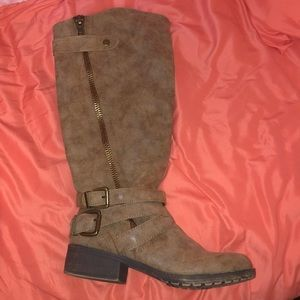 Tan boots with a buckle and zipper detail